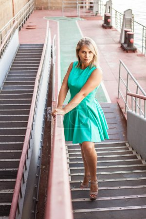 young beautiful girl in a turquoise sundress posing on the steps