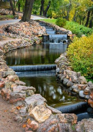 Photo for Stones bordered stream and small artificial waterfalls in  city park at autumn - Royalty Free Image