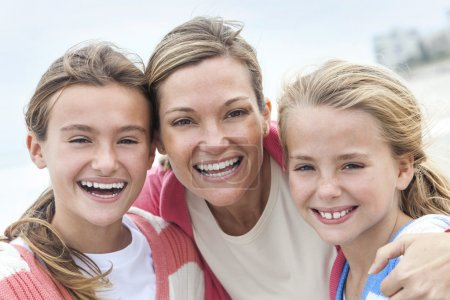 Photo for Happy woman mother and her female girl children having fun together laughing and smiling on vacation at a beach - Royalty Free Image