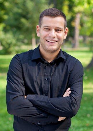 Photo pour Beau mec dans une chemise debout dans le parc - image libre de droit