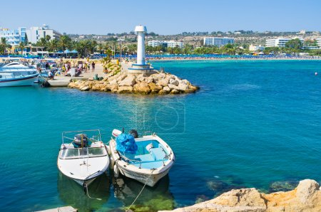 The port of Ayia Napa with the couple of moored boats and the view on the busy beaches on the background, Cyprus.