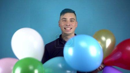 Ein junger Mann mit blauen Haaren hält bunte aufblasbare Bälle in den Händen. Alternative Person, die Spaß mit Bällen auf blauem Hintergrund hat.