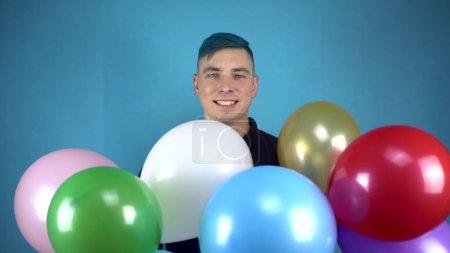 Ein junger Mann mit blauen Haaren hält bunte aufblasbare Bälle in den Händen. Alternativer Mann lächelt mit Bällen auf blauem Hintergrund.