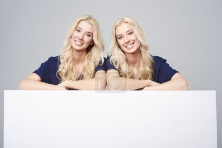 Photo for Twins with empty billboard on light background - Royalty Free Image