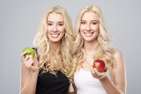 Photo for Twins holding apples. Each girl likes something else - Royalty Free Image