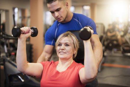 Photo pour Femme avec un dresseur professionnel au gymnase. Faisons-le ensemble - image libre de droit