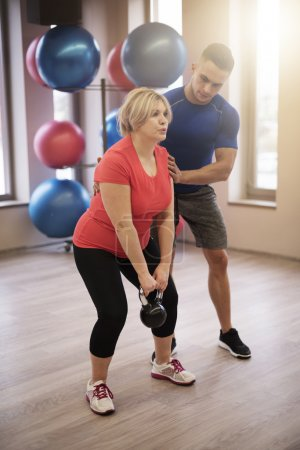 Personal trainer supporting mature woman