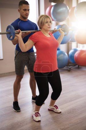 Photo pour Femme d'âge mûr travailler avec l'entraîneur personnel. Exercer avec utilisation d'haltères - image libre de droit