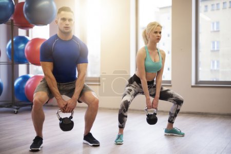 Photo for Fit couple lifting heavy kettles - Royalty Free Image