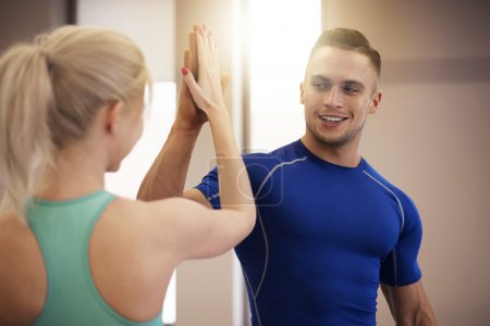 Photo for Couple training together at the gym. Success after reaching the target - Royalty Free Image