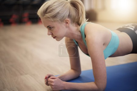 Woman doing plank at health club