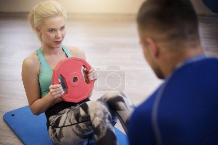 Photo pour Instructeur de fitness aidant femme à la salle de gym. Garder un œil sur son stagiaire - image libre de droit