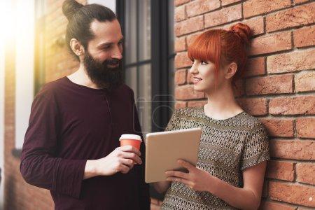 Photo pour Deux jeunes qui se parlent au bureau - image libre de droit