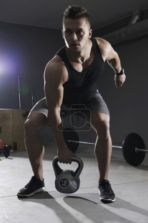 Photo for Man lifting kettlebell with one hand - Royalty Free Image