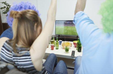 Friends watching football match