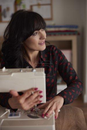 Photo pour Couturière à l'aide de sa machine à coudre - image libre de droit