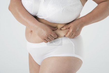 Mature woman squeezing her abdomen