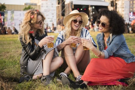 Photo for Women drinking beer and talking gossips during the summer festival - Royalty Free Image