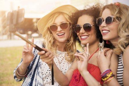Photo pour Les femmes à la mode parlent selfie sur téléphone mobile. Selfie stick comme un outil très utile - image libre de droit