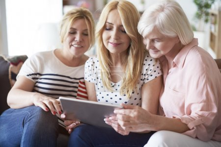 Photo for Mature women browsing some pictures on digital tablet - Royalty Free Image