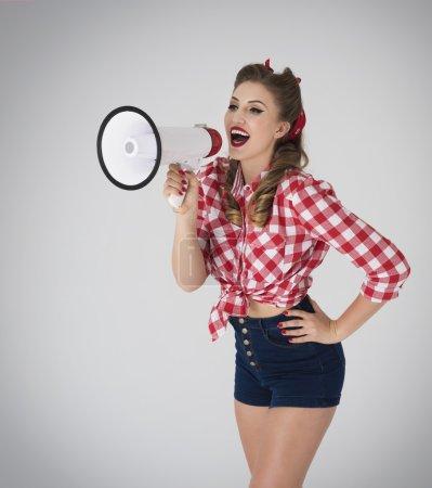 Pin up girl shouting through megaphone