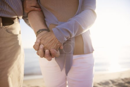 Photo for Senior couple spending time by the sea, Focus on hands holding together. Strong bond between two seniors - Royalty Free Image