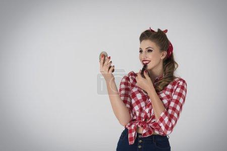 Pin up girl using lipstick