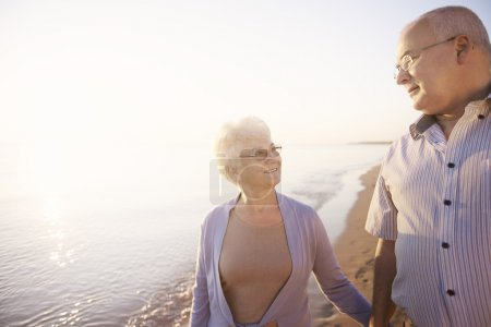 Photo for Senior couple relaxing on the beach and talking about moments from the past - Royalty Free Image