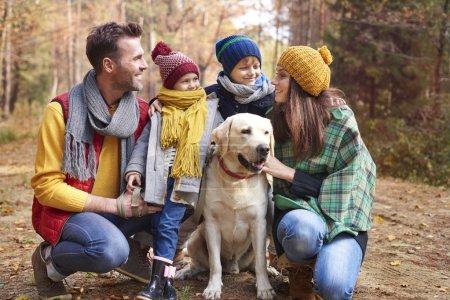 Photo pour On s'aime tellement. Famille heureuse avec chien dans la forêt - image libre de droit