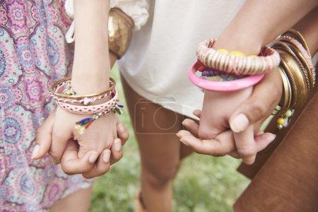 Foto de Ver detalle de las manos llenas de pulseras de colores - Imagen libre de derechos