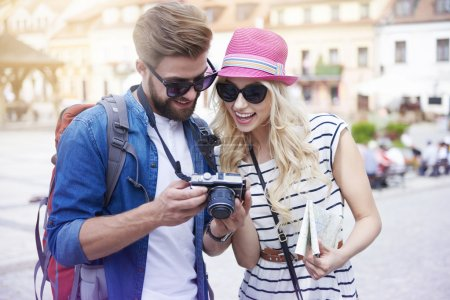 Photo for Happy couple looking on pictures from vacation - Royalty Free Image