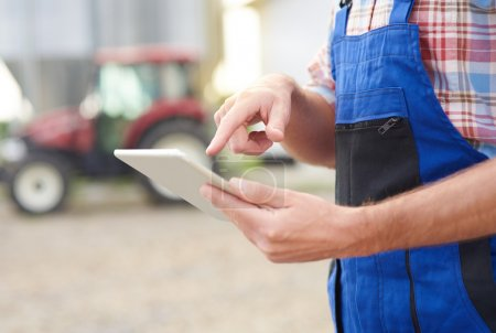 Farmer using  digital tablet at the farm