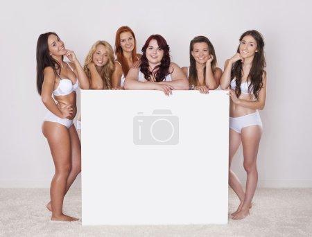 Photo pour Filles naturelles heureuses avec tableau blanc vide - image libre de droit