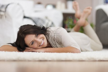 Photo for My new bright carpet is so soft - Laughing woman rests on carpet in interior - Royalty Free Image