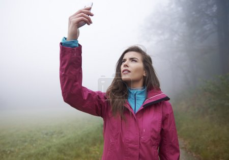 Woman searching signal for mobile phone