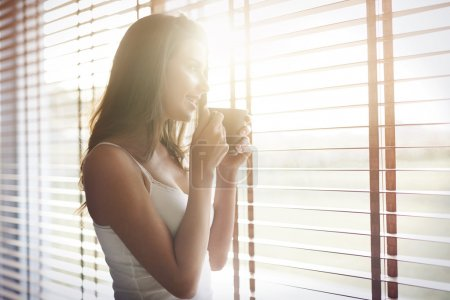 Photo for Woman in bedroom with coffee. Morning sunshine and good coffee always makes me in a good mood - Royalty Free Image
