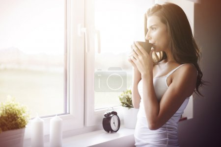 Photo pour Young woman in bedroom drinking morning coffee. What a great way to wake up! - image libre de droit