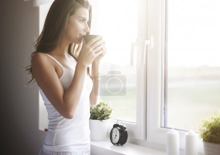 Photo for Woman near the window with a cup of coffee. Morning coffee is my daily routine. - Royalty Free Image