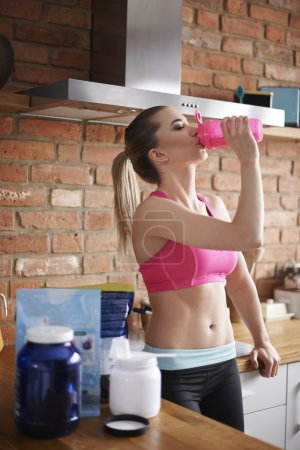 Photo pour Woman with Protein drink standing in the kitchen - image libre de droit