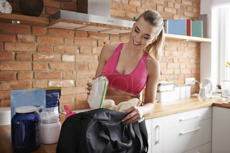 Photo for Woman Packing bag for the gym at the kitchen - Royalty Free Image