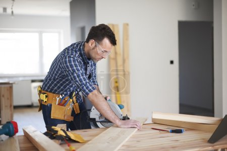 Young handsome carpenter man planning to work...