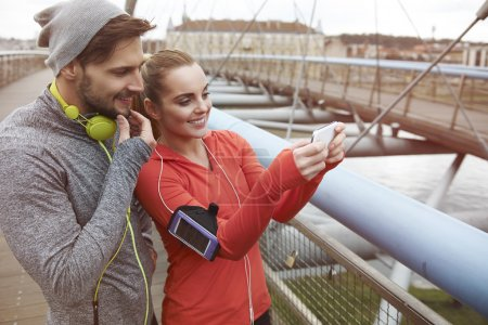 Sporty couple using smartphone