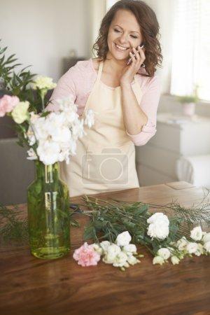 Photo pour Femme parle sur téléphone mobile et crée le bouquet avec des fleurs blanches - image libre de droit