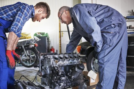 Two mechanics  repairing car's engine