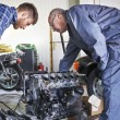 Two mechanics at the service trying to repair car'...