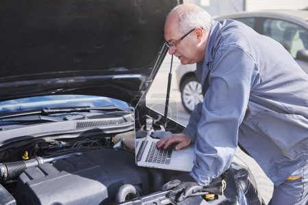 Professional mechanic using technology at work