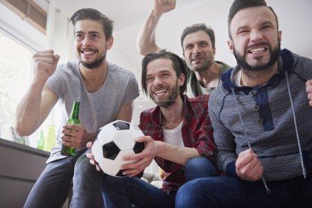 Group of men watching football match