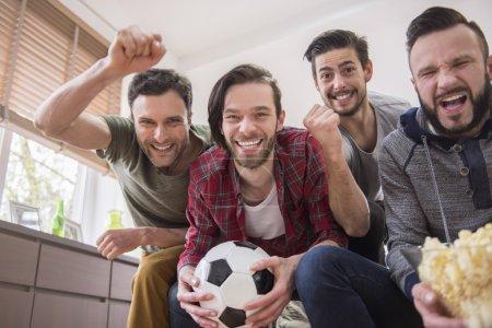 Men watching soccer match.