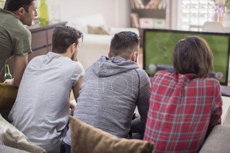 Group of men watching soccer match