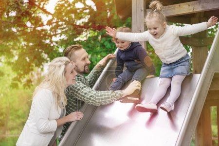 Photo pour Belle jeune famille dans le parc s'amuser avec de petits enfants - image libre de droit